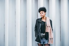 Black girl with vintage photocamera near patterned wall royalty free stock image