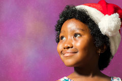 Black girl wearing christmas hat looking at corner. Close up face shot of little african girl wearing christmas hat. Kid staring at upper corner against Royalty Free Stock Photography