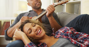 Black girlfriend enjoying being serenaded to by boyfriend Royalty Free Stock Images