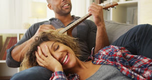 Black girlfriend enjoying being serenaded to by boyfriend. At home stock image