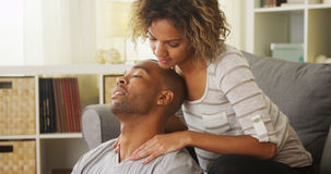 Black girlfriend giving boyfriend neck massage Stock Photos