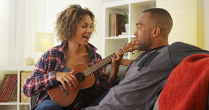 Black girlfriend serenading her boyfriend with ukulele Royalty Free Stock Photos