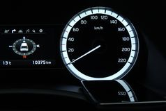 Black glass surface of smartphone displaying dashboard digits inside a vehicle. Car speedometer digits in reflection on the glass display of smartphone close up Stock Image