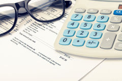 Black glasses and calculator over utility bill. Filtered image: cross processed vintage effect. stock photography