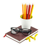 Black glasses and color pencils in white mug placed on notebook. Royalty Free Stock Photos