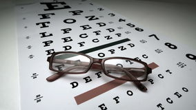 Black glasses falling onto eye test stock video footage