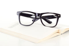 Black glasses on open book Stock Photography