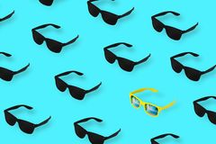 Black glasses on pastel blue background. Among the many black glasses alone yellow. Minimum summer concept royalty free stock photography