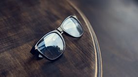 Black glasses with reflection. On the wooden table royalty free stock photo