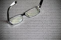 Black glasses on a white paper background with random letters of the English alphabet, hidden words stock image