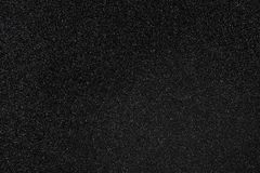 Black Glitter Background. Coal black colored sand paper textured background with sparkles and glitters stock photo