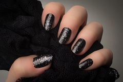 Black glittered nails. Female hand with black nails and silver glitters is holding black textile on gray background Stock Image