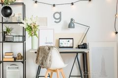 Nordic work area with fur. Black globe on shelf and flowers in white vase on nordic work area with fur on chair. Home office design concept royalty free stock photography