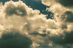 Black gloomy storm clouds with flashes of sunlight royalty free stock image