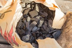 Black glossy coal for bonfire and bbq from supermarket inside a craft brown paper bag. stock photo