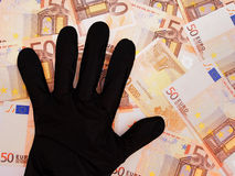 Black gloved hand on Euro currency, financial curruption. Stock Image