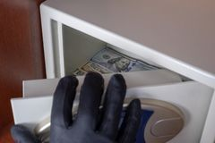 The black-gloved right hand opens the safe deposit box door. Theft of dollars from the safe. Concept of protection and security of. Theft of dollars from the stock photography