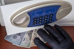 The black-gloved right hand takes money from the open door of the safe deposit box. Theft of dollars from the safe. Concept of. The black-gloved right hand takes royalty free stock photo