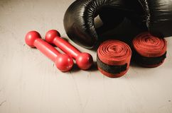 black gloves and red dumbbells and bandage/boxing concept with black gloves and red dumbbells and bandage stock images