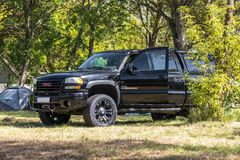 Black GMC 2500 HD. Parked at a campsite next to a tent in the shade under trees Royalty Free Stock Images