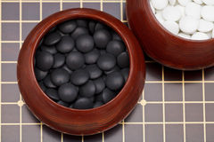 Black go stones in wooden bowl on go board Stock Photos