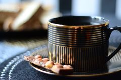 Black and gold coffee cup with chocolate bar. Proposal for a relaxing afternoon with a book royalty free stock photos