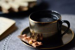 Black and gold coffee cup with chocolate bar. Proposal for a relaxing afternoon with a book stock images