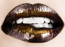 Black gold lips biting. Woman biting her lips with black glossy lipstick and gold powder shine