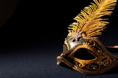 Black and gold mask. On a black background Stock Photos