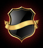 Black and gold shield and ribbon stock photos