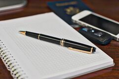 Black and Gold Twist Pen Near White Smartphone Stock Images
