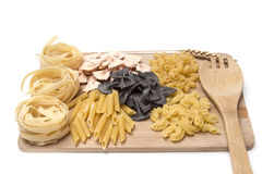 Black and golden macaroni, pastes  on a wooden board Royalty Free Stock Photography