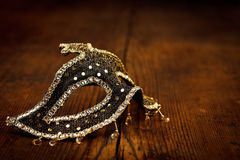 Black and golden mask on rustic table Stock Image