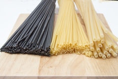 Black and golden spaghetti, pastes  on a wooden board Royalty Free Stock Images