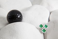 Black golf ball and four leaf clovers Royalty Free Stock Images