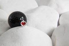 Black golf ball and red heart Stock Image