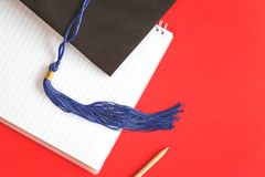 Black graduation cap with blue ribbon on red. Black Graduation Cap with notebook on red background. Masters or Bachelors Degree thesis writing and higher royalty free stock photography