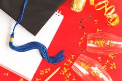 Black graduation cap with blue ribbon on red. Black Graduation Cap with notebook on red background. University or college graduation celebration with golden stock images