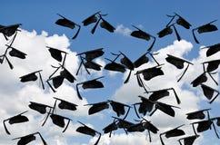 Black graduation caps in sky Stock Photography