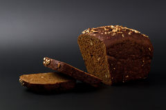 Black grain bread on a black Royalty Free Stock Images