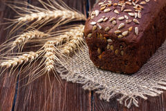 Black grain bread and wheat on the wooden. Table Royalty Free Stock Photography
