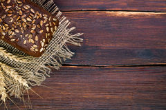 Black grain bread and wheat on the wooden. Table Royalty Free Stock Image
