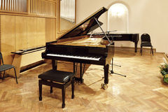 Black grand piano. On a bare stage stock image