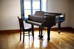 Black grand piano. In room with window royalty free stock images