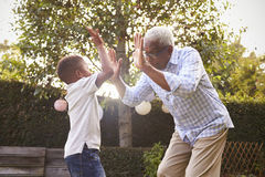 Free Black Grandfather Playing With His Grandson In A Garden Royalty Free Stock Image - 85210136