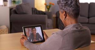 Black grandma video chatting on tablet stock images