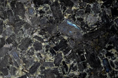 Black Granite Stone Background. Black background of granite stone on kitchen countertop material with chunks of rock and stone material Stock Photo