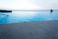 Black granite stone pool edge. Focus on black granite stone pool edge with people in swimming pool background used for display or montage object Stock Photography