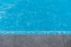 Black granite stone pool edge. Focus on black granite stone pool edge with see through underwater floor tiles background used for display or montage object Stock Photos