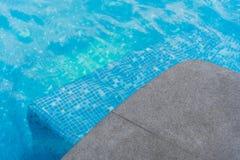 Black granite stone pool edge. Focus on corner black granite stone pool edge with see through underwater floor tiles background used for display or montage Stock Photography